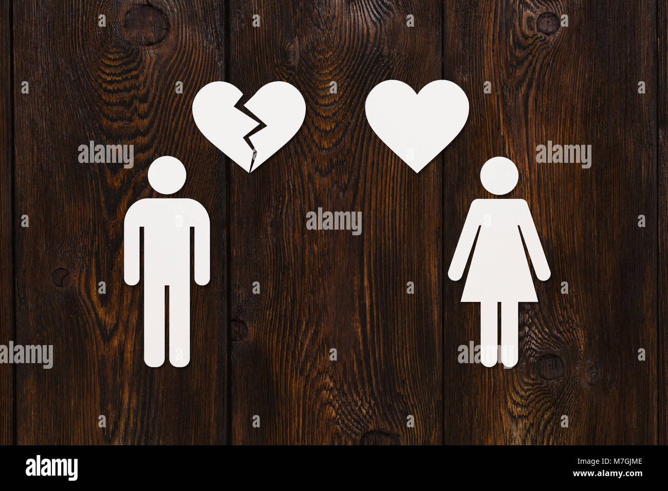Paper woman with heart and man with broken one on wooden background. Unrequited love or divorce concept. Abstract - Stock Image