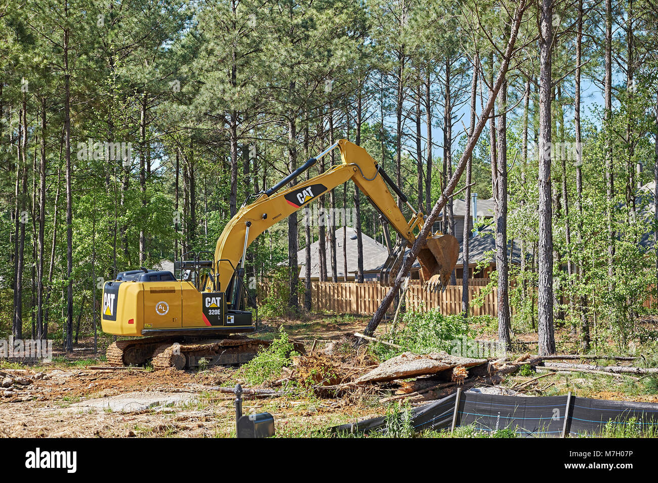 Digger or excavator clearing land for new construction building lot in Pike Road Alabama, USA. - Stock Image