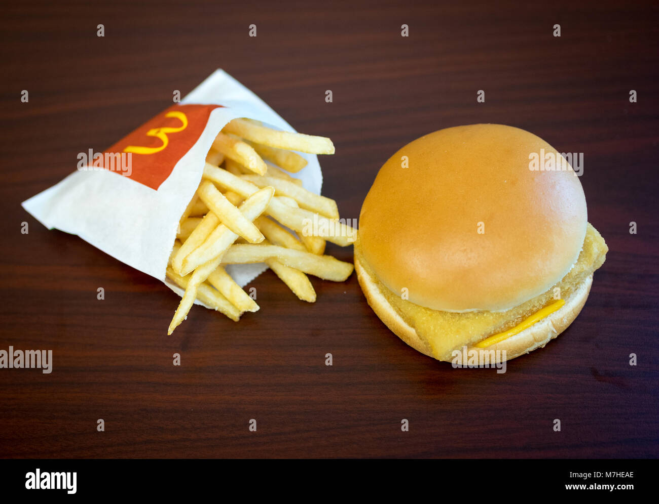 A McDonald's Filet-O-Fish, a fish sandwich, and a small french fries. - Stock Image