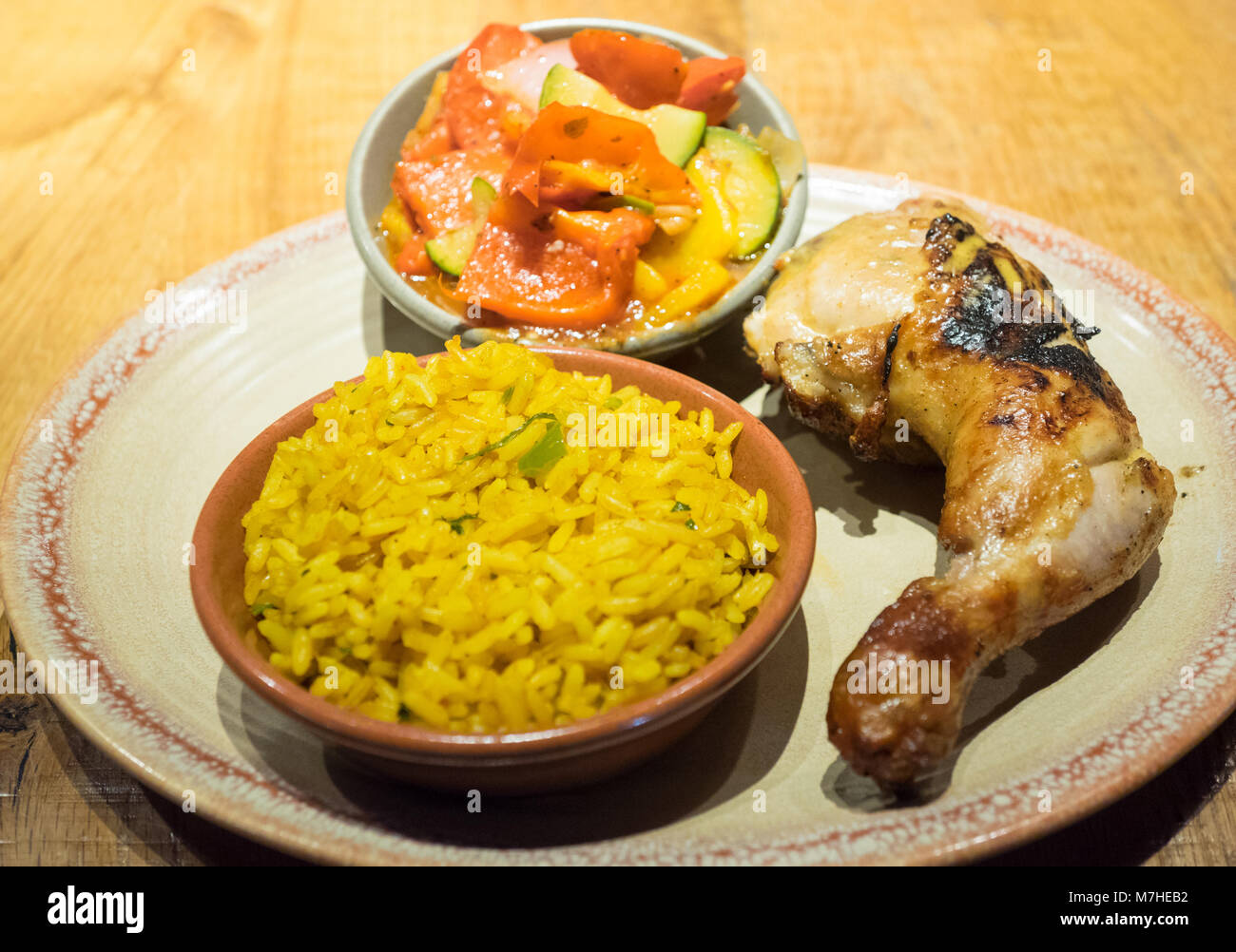 Peri-peri quarter chicken with sides of spiced rice and peri-peri vegetables from Nando's, a casual dining chain - Stock Image