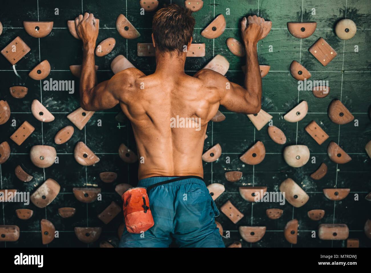 Muscular man climbing wall at an indoor wall climbing centre. Rock climber practicing climbing at an indoor climbing - Stock Image