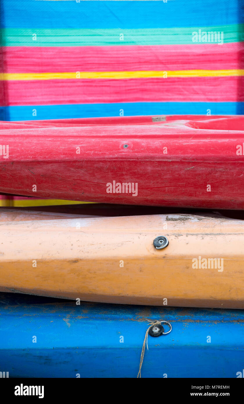 Colourful kayaks stacked on top of each other - Stock Image