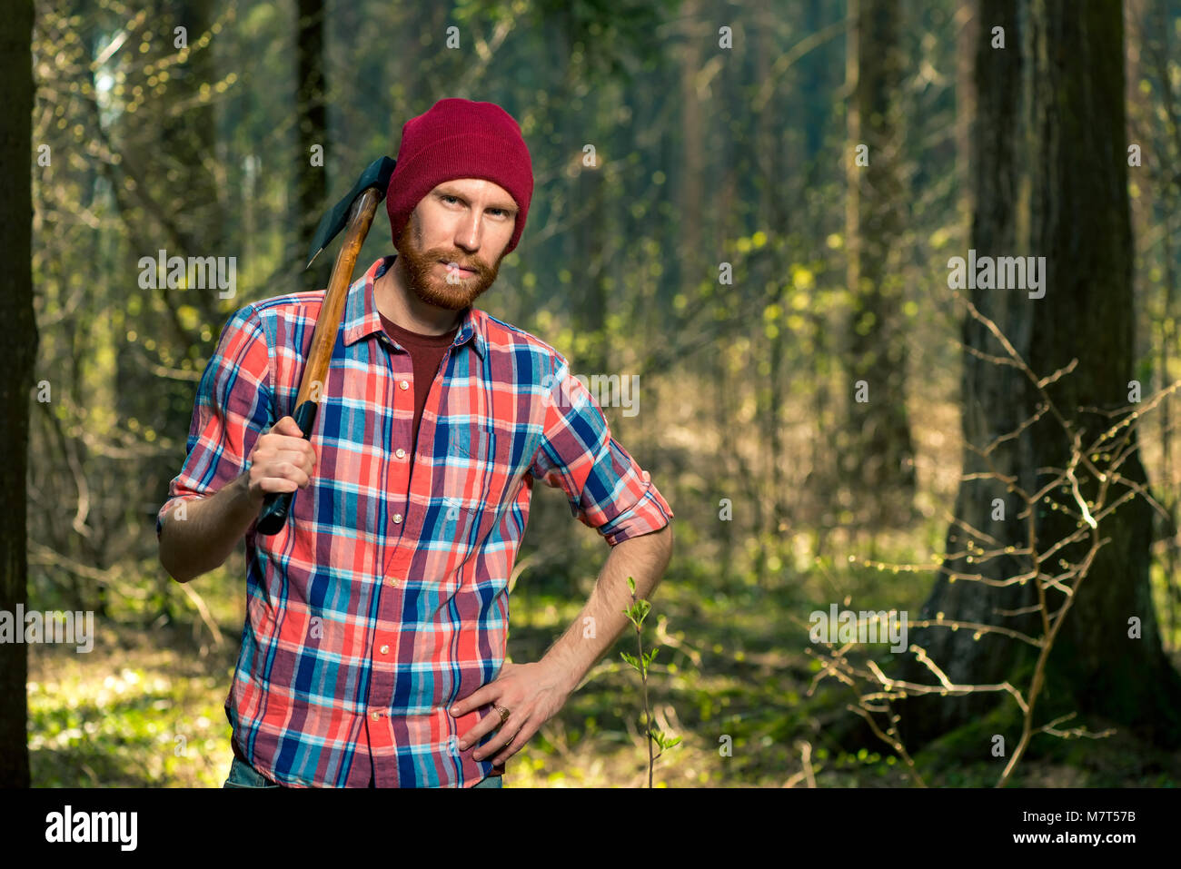 392c3899061 portrait of a forester with a beard and an ax in a shirt in the woods
