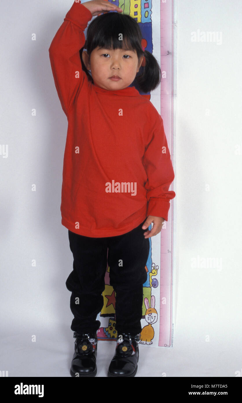 little Chinese girl standing in front of height chart - Stock Image