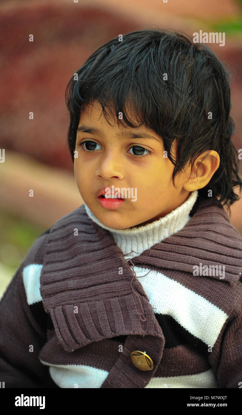 The age of innocence - a beautiful Indian boy poses for the camera. Portrait of young child with large eyes, wearing - Stock Image
