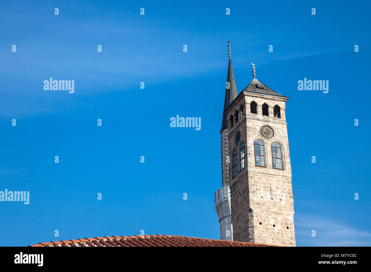 Minaret of the Gazi Husrev begova Mosque next to the clocktower of Sarajevo bazaar, in Bosnia and Herzegovina   - Stock Image