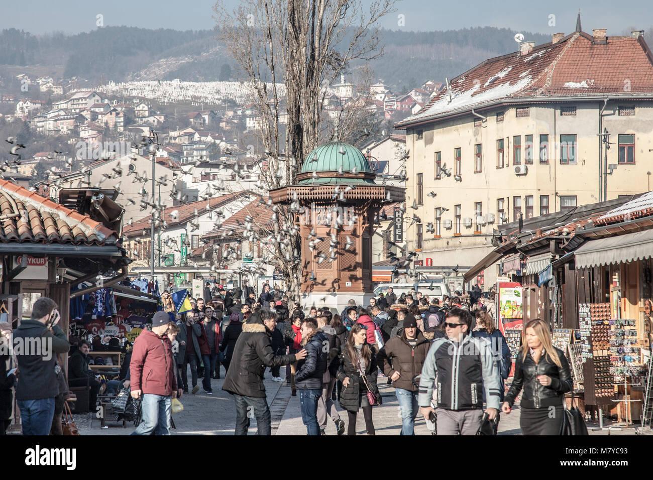 SARAJEVO, BOSNIA AND HERZEGOVINA - FEBRUARY 16, 2018: Pigeons flying over the Bascarsija square Sebilj fountain. - Stock Image