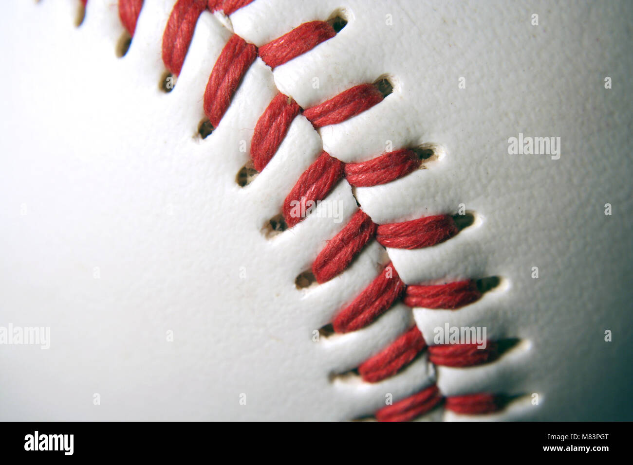A white Baseball Macro with red stitching - Stock Image