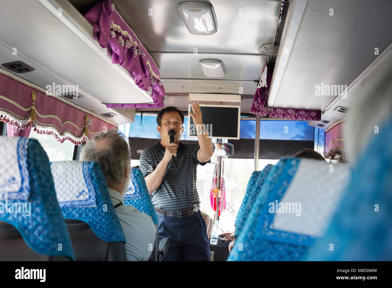 A tour guide talking to tourists on a coach trip, Cambodia, Asia Stock Photo