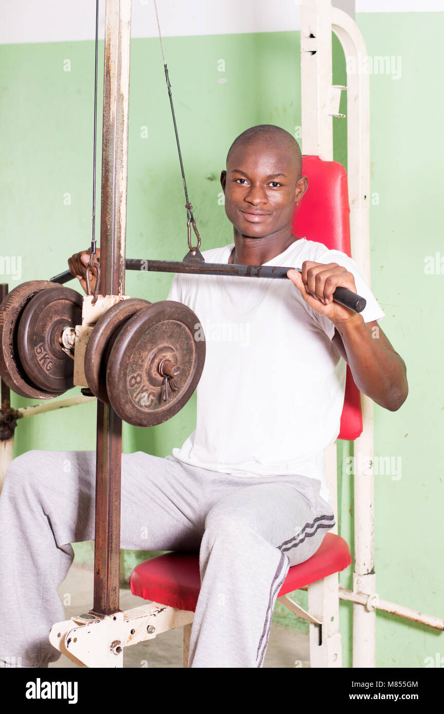 Young man doing weight training by pulling a weight by a pulley. - Stock Image