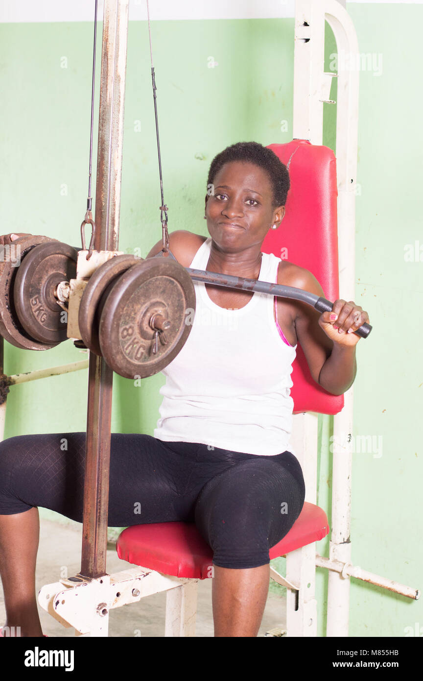 Young woman doing weight training by lifting weights. - Stock Image