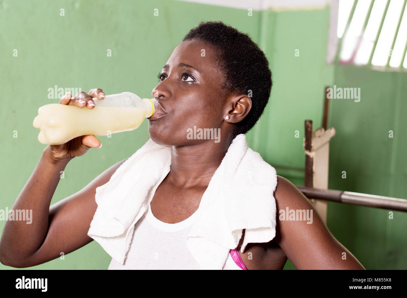 Young athlete drinks fruit juice after sport. - Stock Image