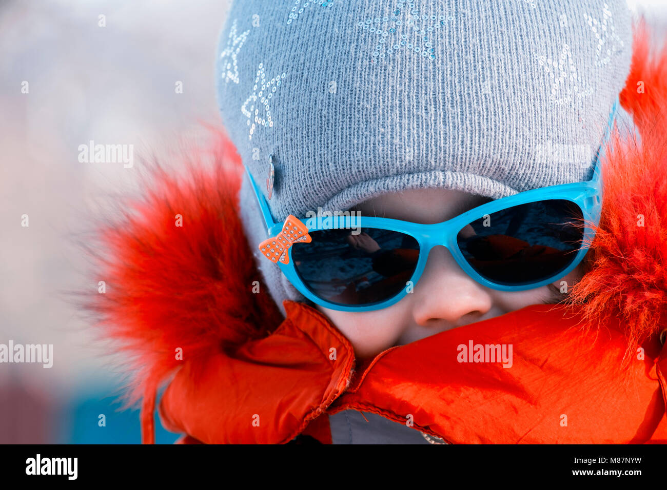 Portrait of a little girl in sunglasses in winter - Stock Image