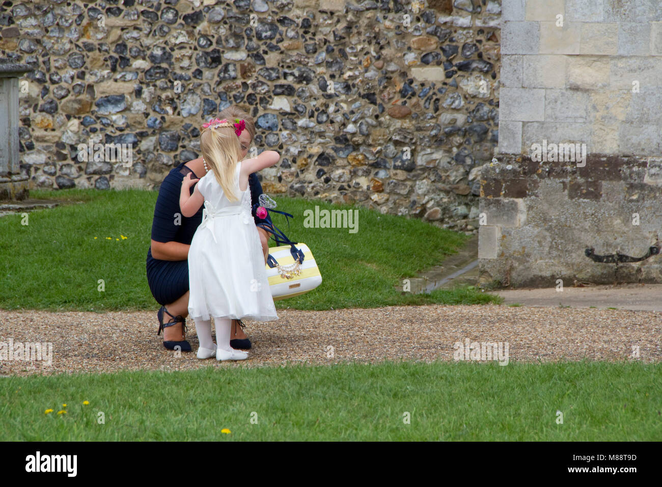 Woman squats to talk with very young bridesmaid - Stock Image