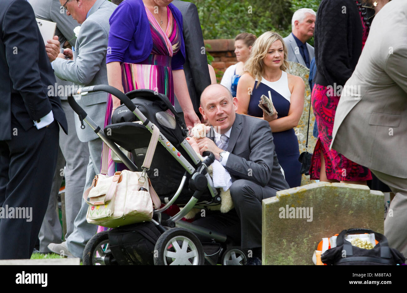 At a wedding a middle aged man squats to entertain a baby in a buggy - Stock Image