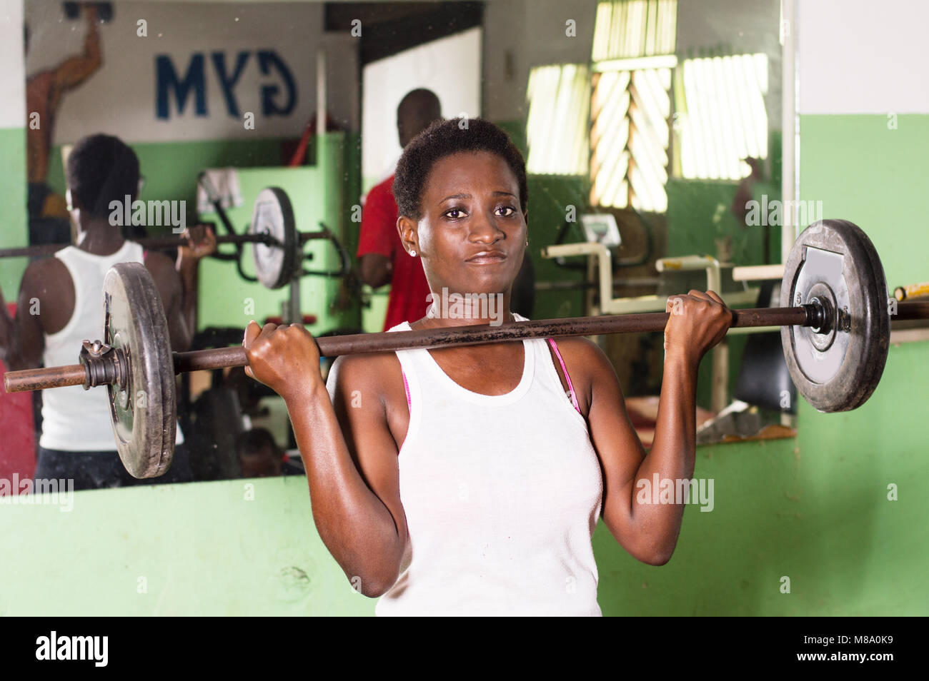 Young athlete, weight lifted at chest level looks at the camera. - Stock Image