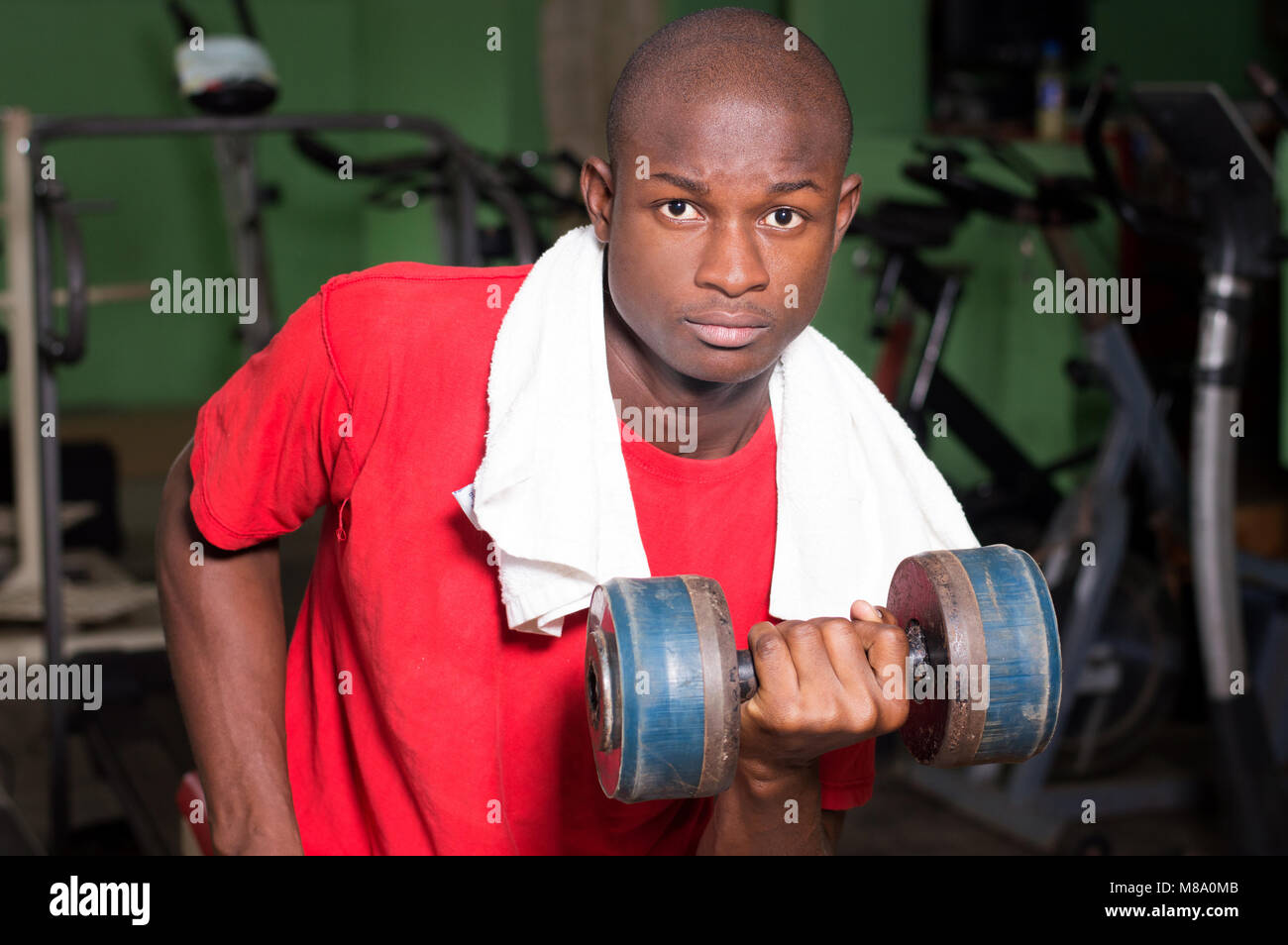 Young man doing weight lifting exercises with a weight in hand in a gym. - Stock Image