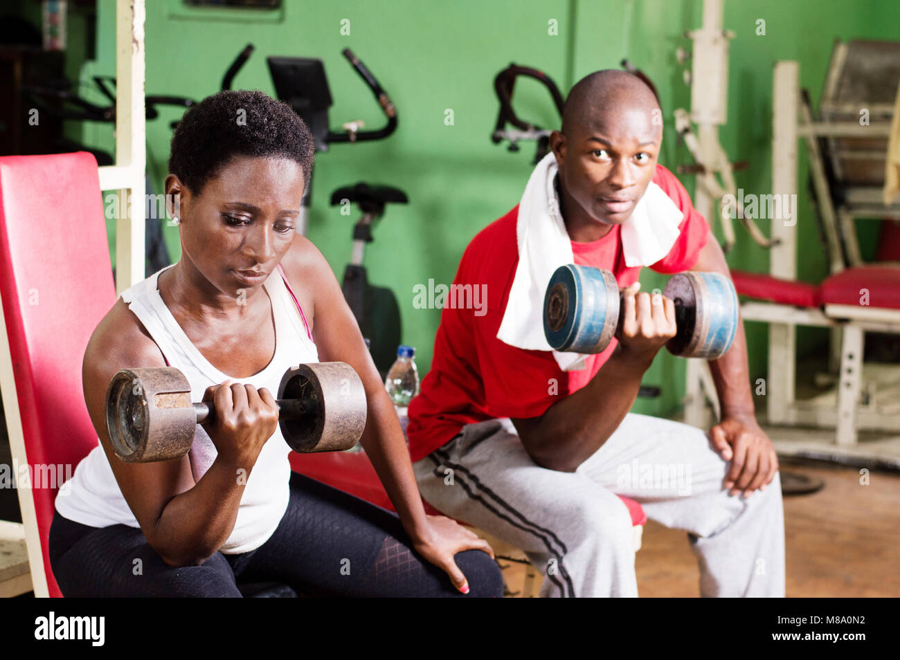 Young woman and coach do weight lifting in a gym. - Stock Image