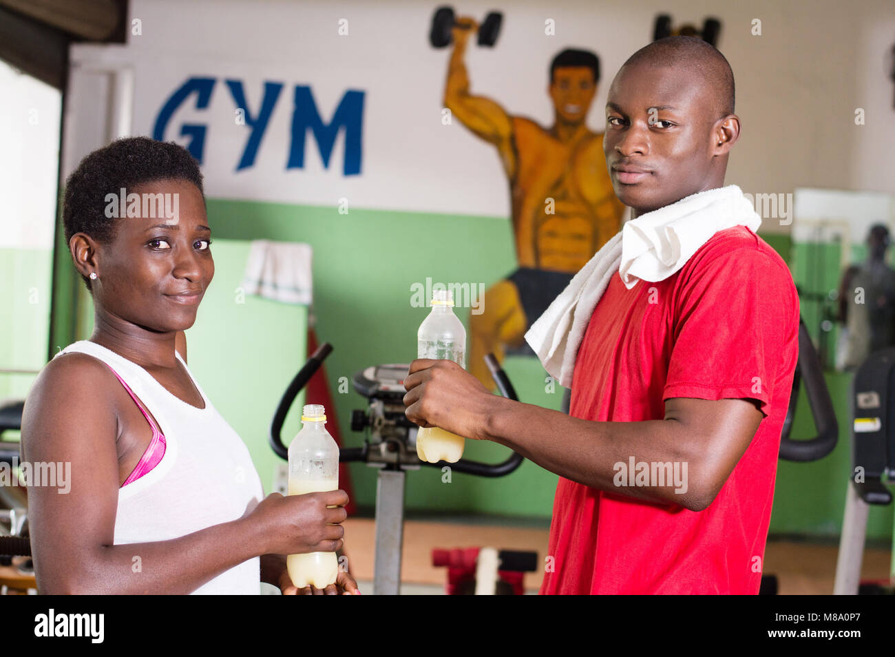 Young woman and her coach hold bottles of fruit juice in hand in the gym. - Stock Image