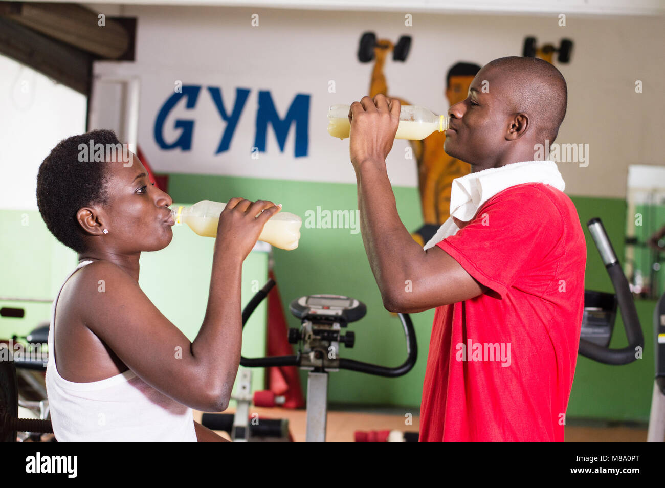 Young woman and her coach drink fruit juice after intensive training. - Stock Image