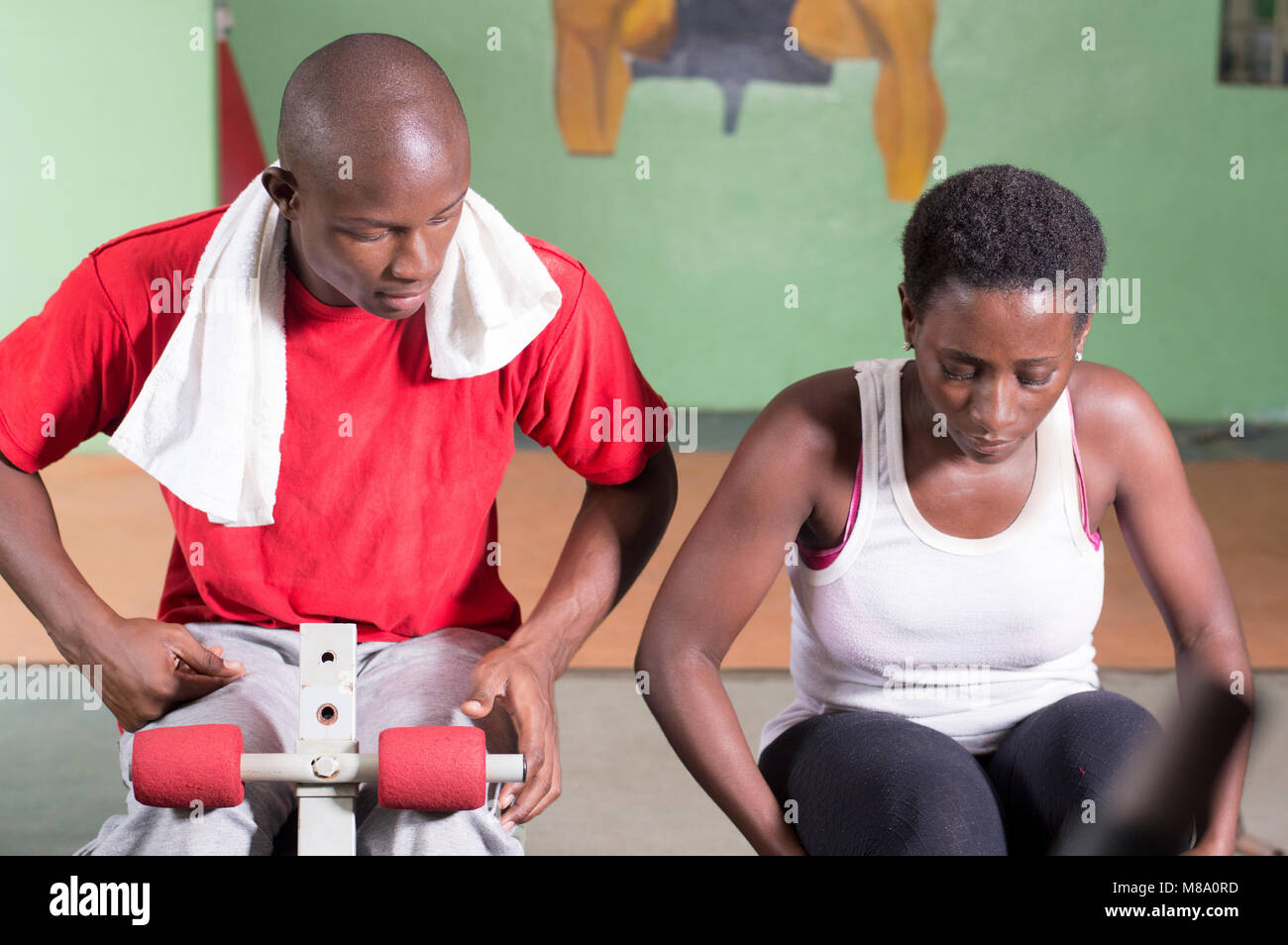 Young woman in training session on a bench with her coach in a gym. - Stock Image