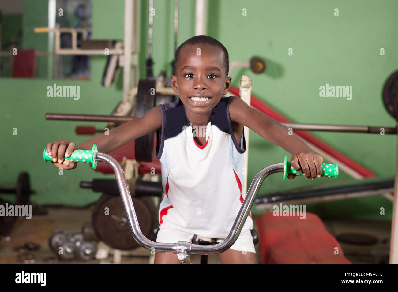 Smiling little boy trains on a bike to acquire fitness. - Stock Image