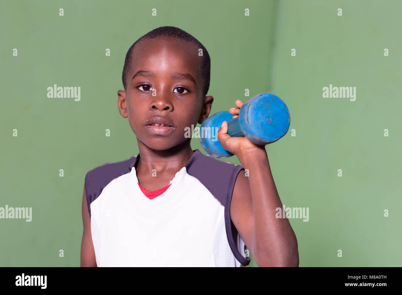 Child training to fitness in a gym by lifting weights - Stock Image