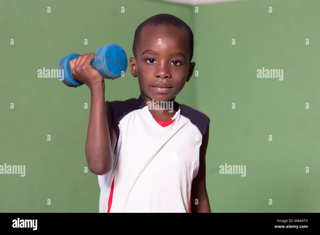 Child training to fitness in a gym by lifting weights. - Stock Image