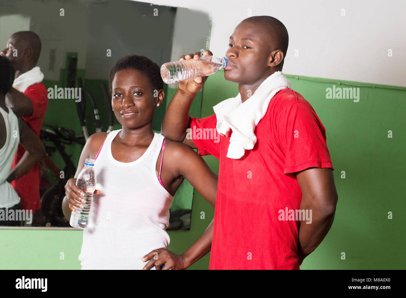 Young woman and her coach drink water from the gym. - Stock Image