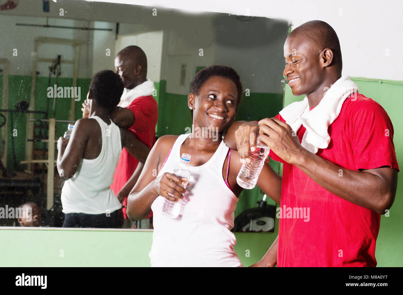 Young woman and her coach look at each other smiling with bottles of water in hand. - Stock Image