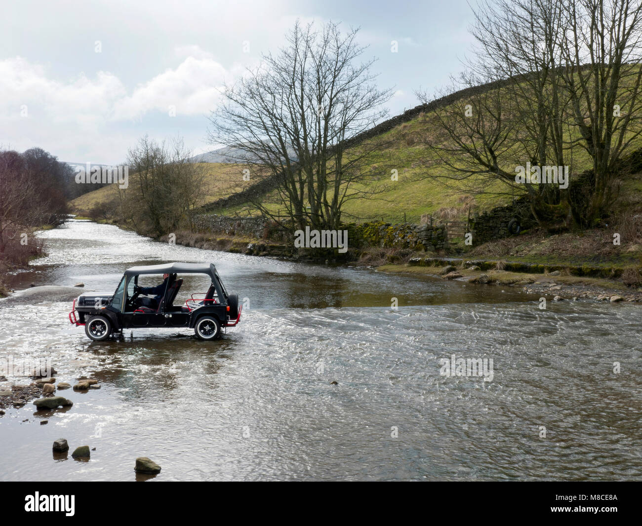Mini Moke crossing Gayle Beck ford in Gayle near Hawes North Yorkshire UK - Stock Image