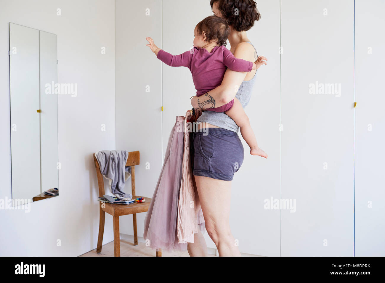 Mother holding baby girl, whilst looking in mirror, deciding what to wear - Stock Image