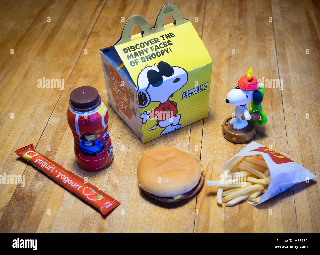 A McDonald's Happy Meal with a cheeseburger, French fries, chocolate milk, yogurt tube, and Snoopy toy. - Stock Image
