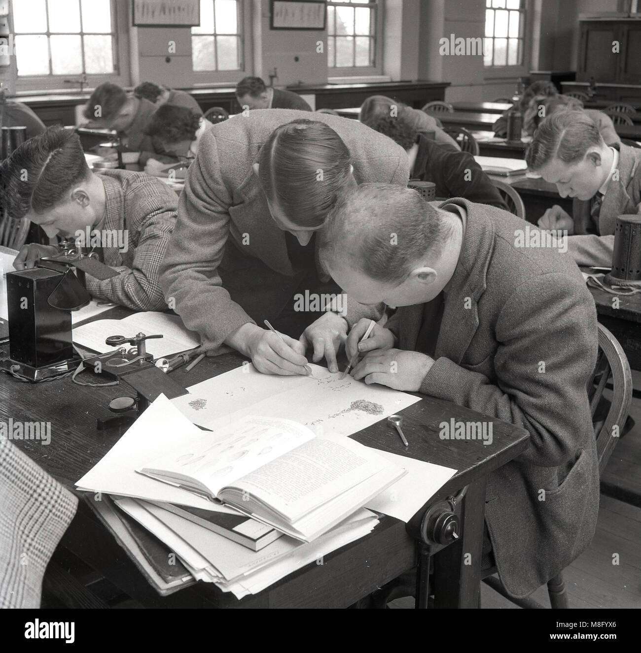 Circa late 1940s, teacher helping a male student with his class work at a technical college, England, UK. In post - Stock Image