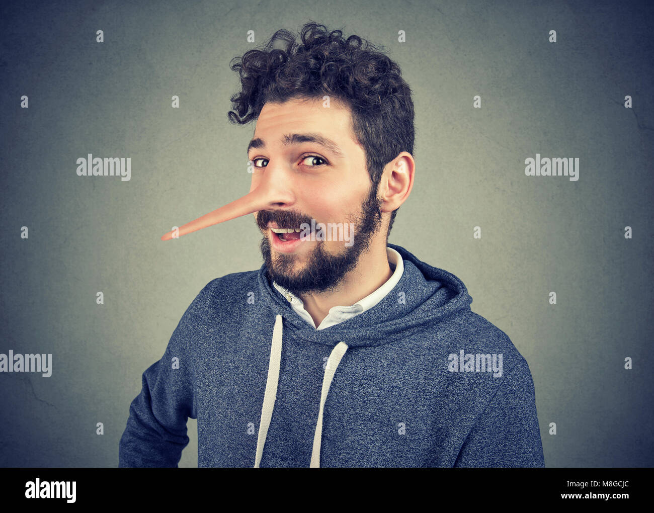 Liar man with long nose isolated on gray background. Human emotions, feelings. - Stock Image