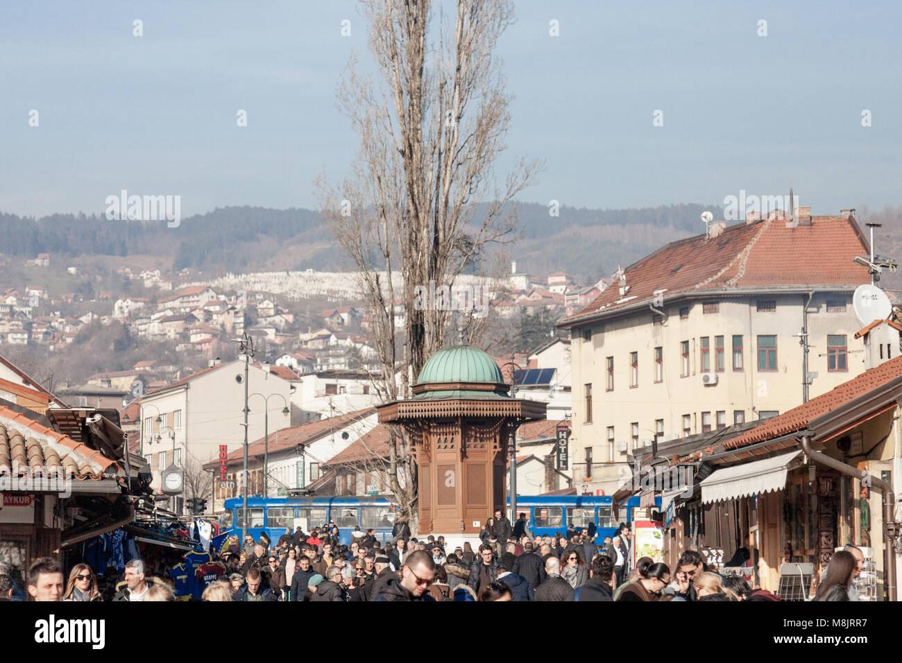 SARAJEVO, BOSNIA AND HERZEGOVINA - FEBRUARY 17, 2018: Crowd of tourists on the Bascarsija square Sebilj fountain. - Stock Image