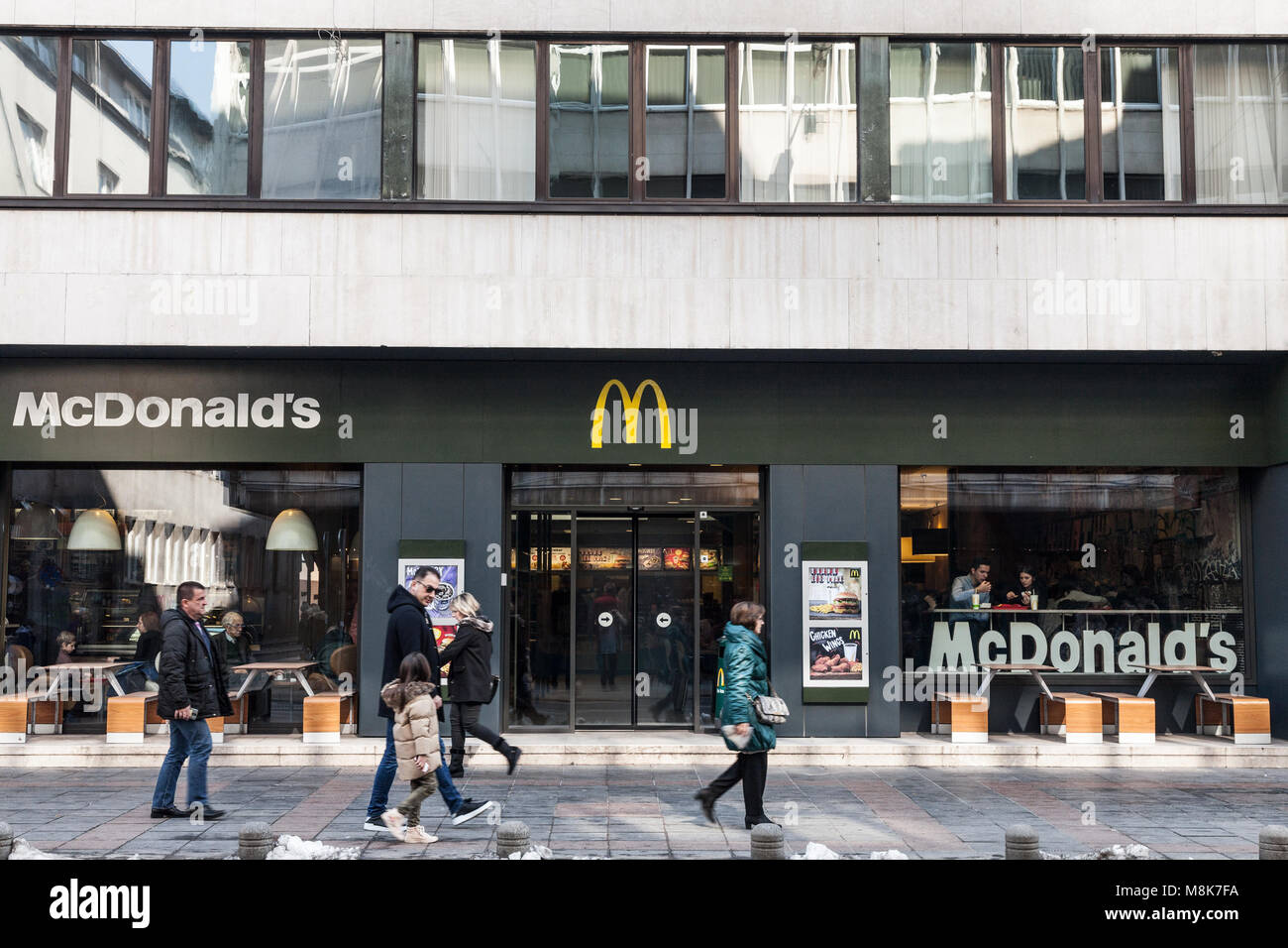 SARAJEVO, BOSNIA - FEBRUARY 17, 2018: Pedestrians passing in front of a Mc Donald's restaurant on the main street - Stock Image