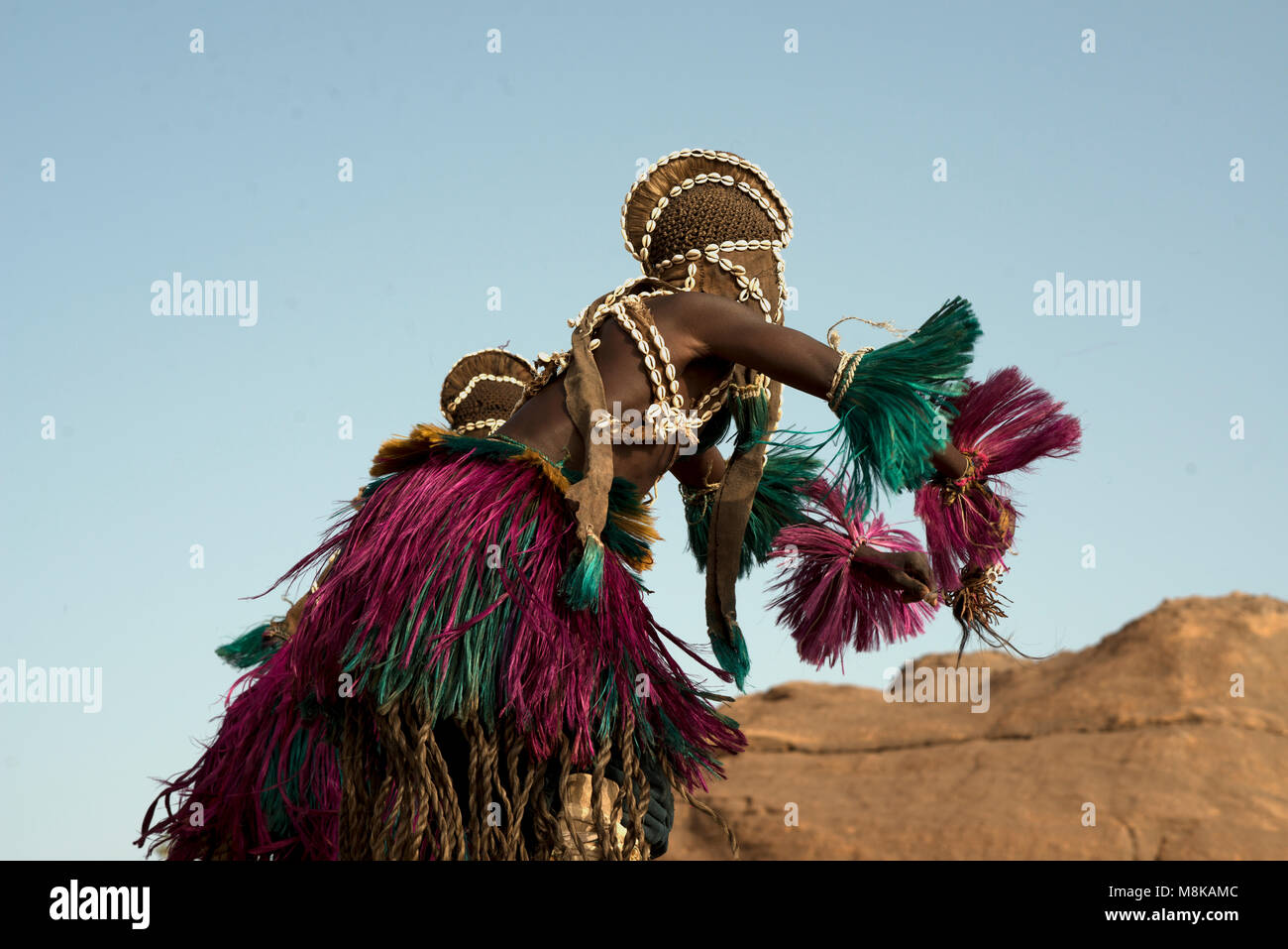 A Dogon man is a masked dancer as he participates in an ancient tribal dance ritual in his clifftop village in Mali, - Stock Image