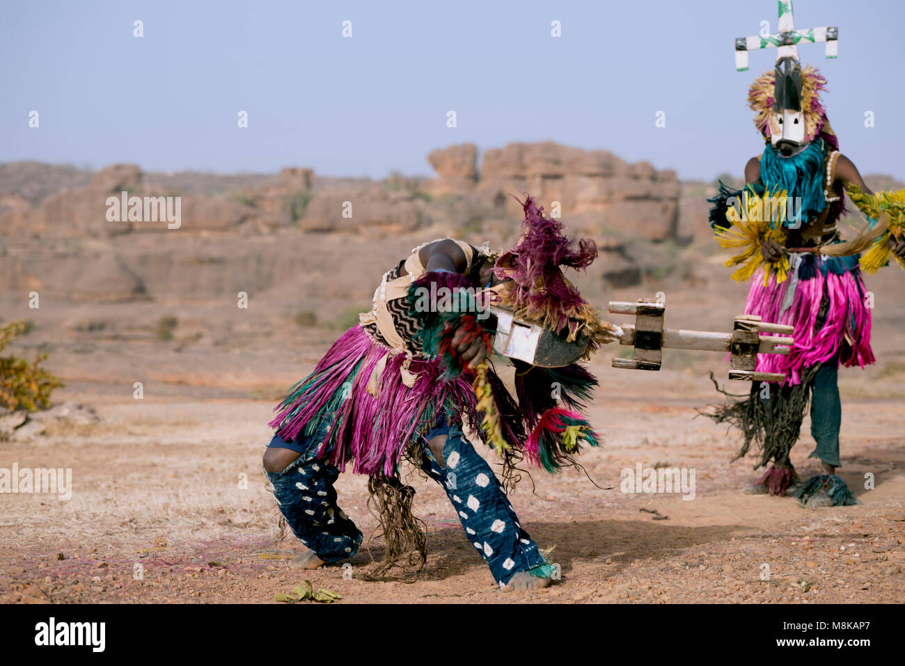 A Dogon man twists and turns while wearing a large mask and headdress and performing a traditional tribal dance. - Stock Image
