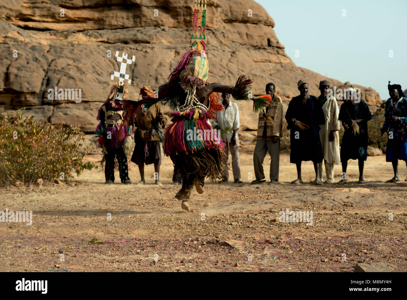 A group of Dogon masked dancers watch a man wearing a towering headdress perform his part in a traditional dance. - Stock Image