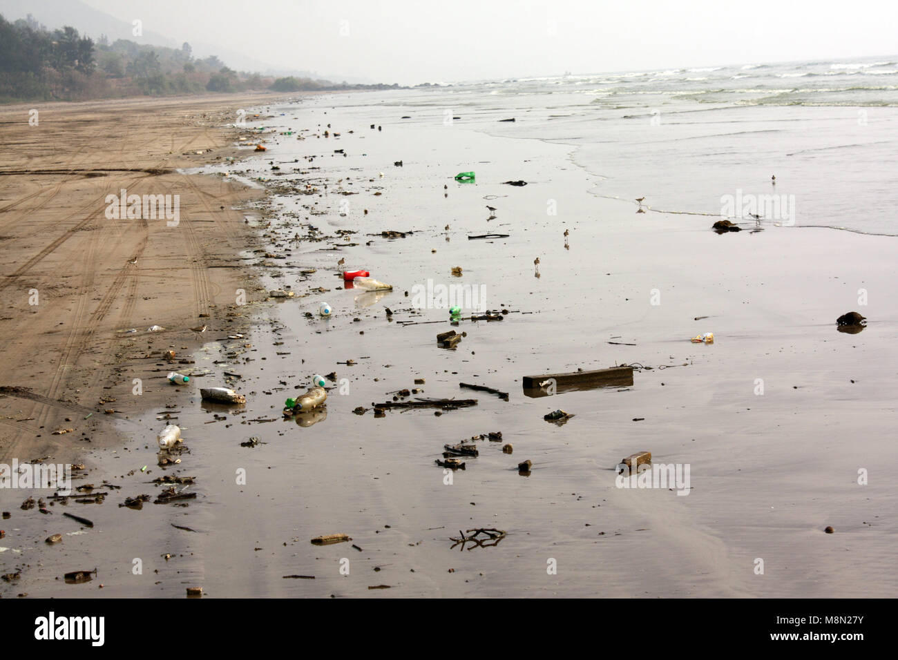 A beach which has thrown up all the tourist garbage during a high tide. - Stock Image