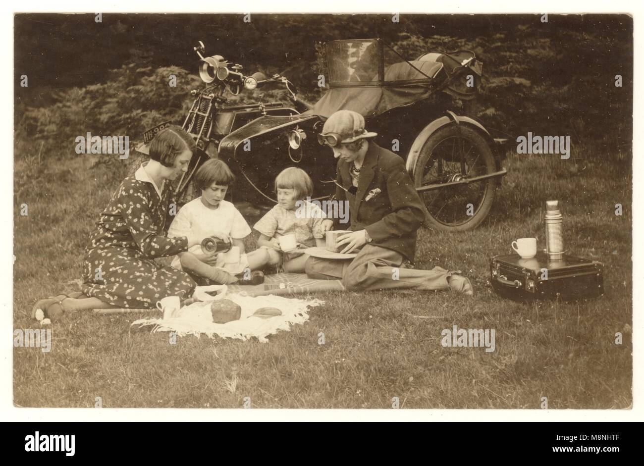 1920's postcard of grandmother with children and their mother, having a picnic beside a motorbike, with a side - Stock Image