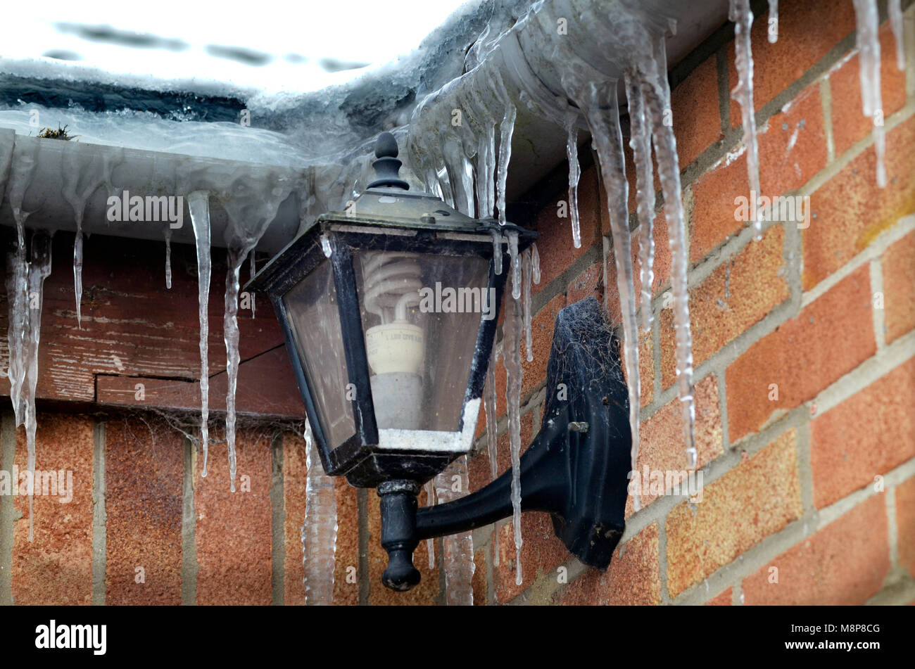 frozen icicles hanging from house gutteering during prolonged cold snap - Stock Image