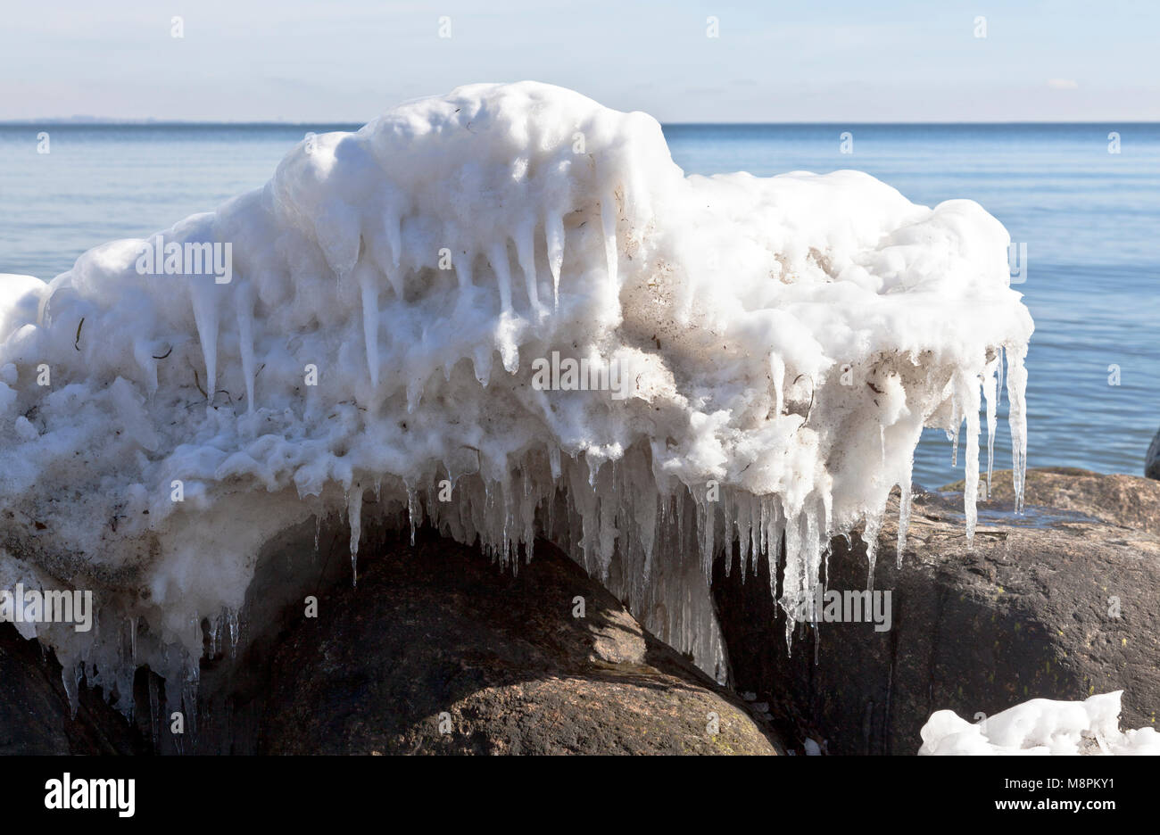 Melting ice formations and icicles on an early, sunny spring day on the coast at Skodsborg after a long  cold spell - Stock Image