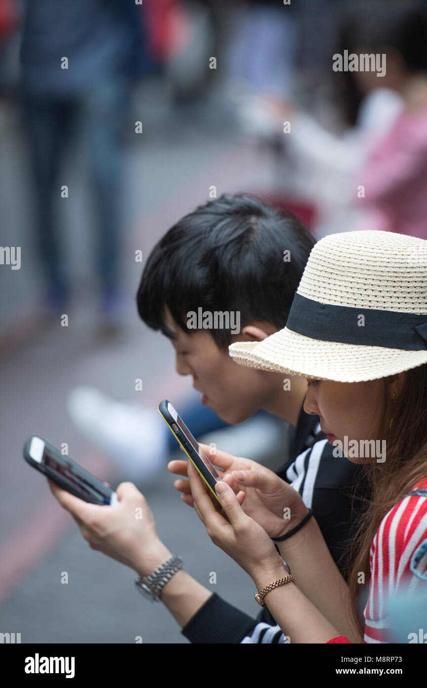 Two young adults using mobile phones on the streets of Shanghai in China - Stock Image