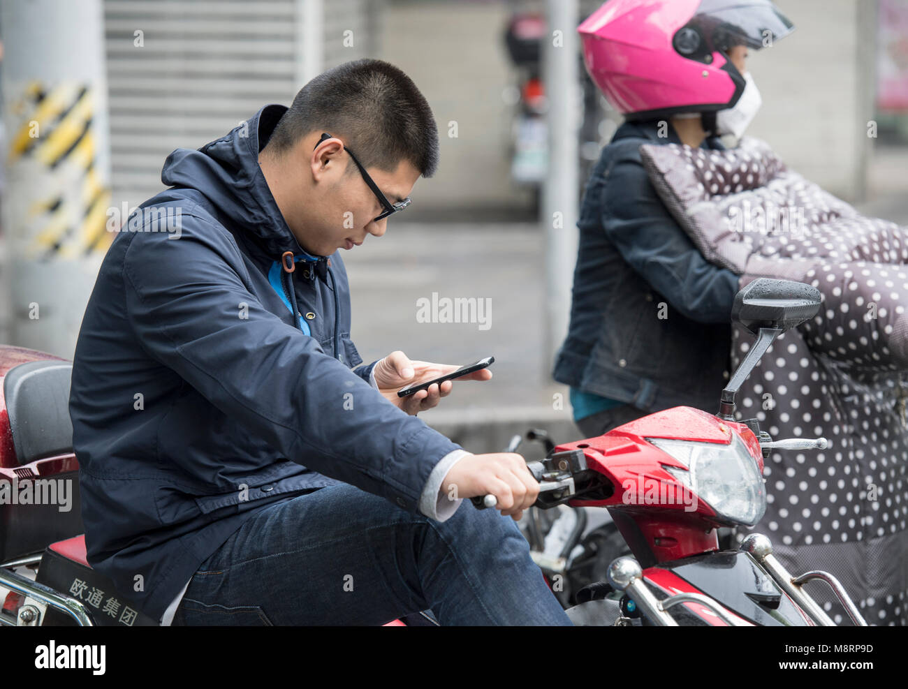 Man checking his mobile phone while sitting on a scooter in Shanghai, China - Stock Image