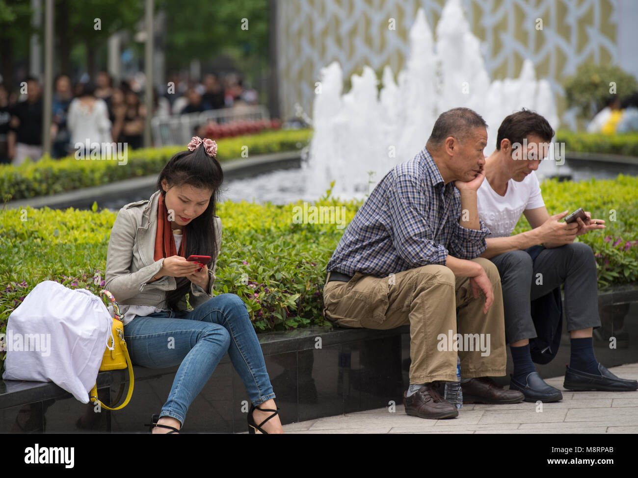 People using their mobile phones in Shanghai, China - Stock Image