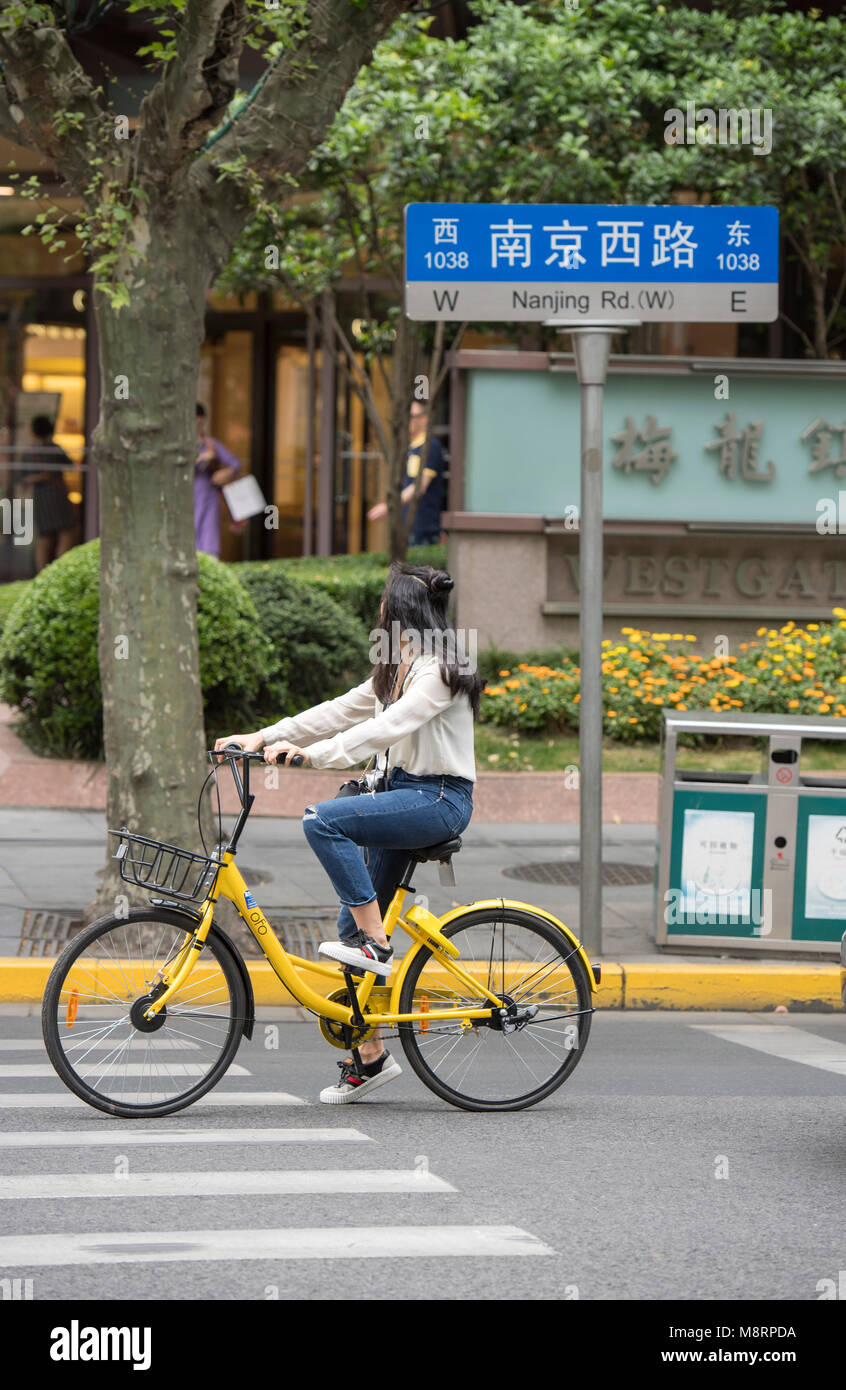 Young woman riding a yellow bicycle on the streets of Shanghai in China - Stock Image