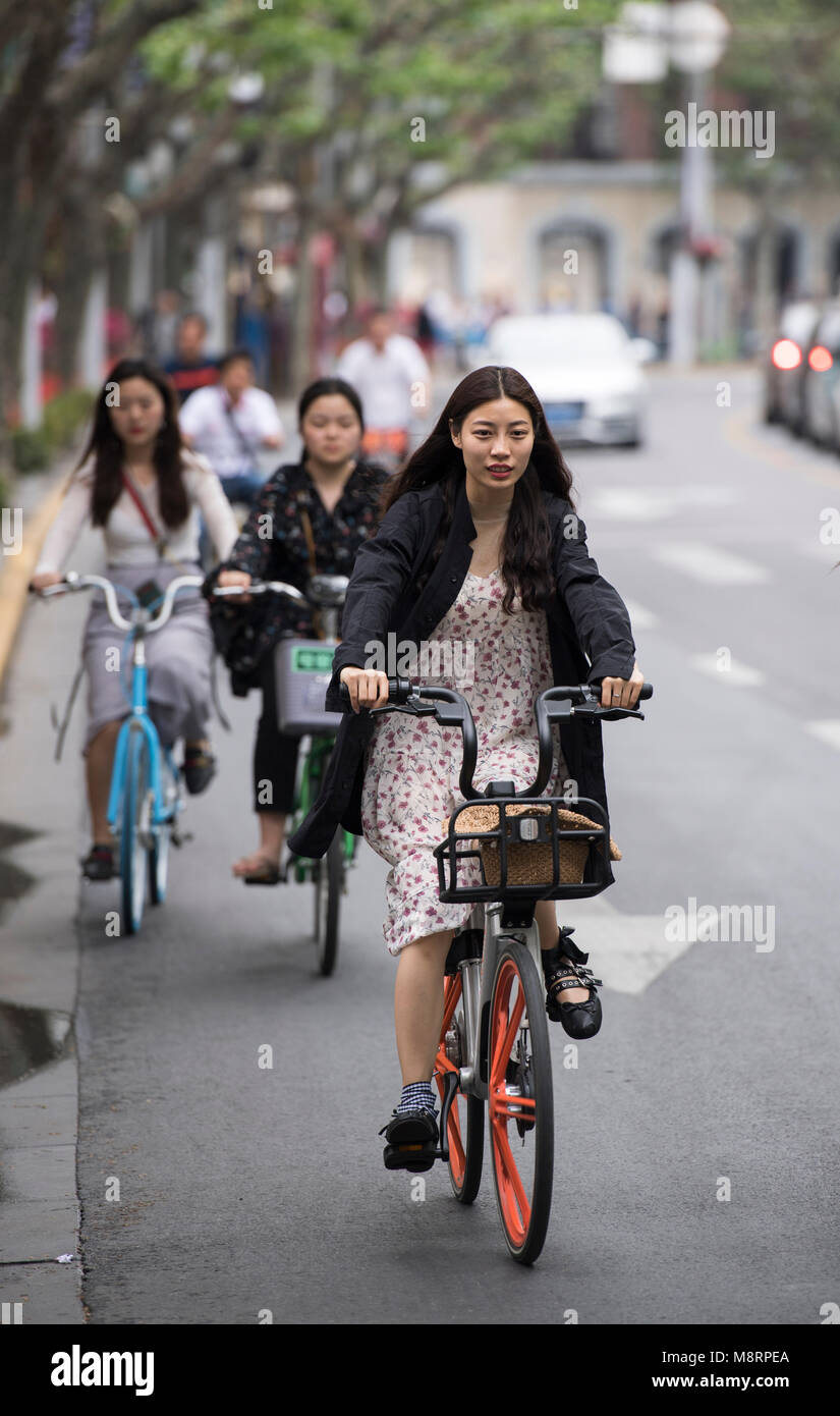 People riding bikes on the streets of Shanghai in China - Stock Image