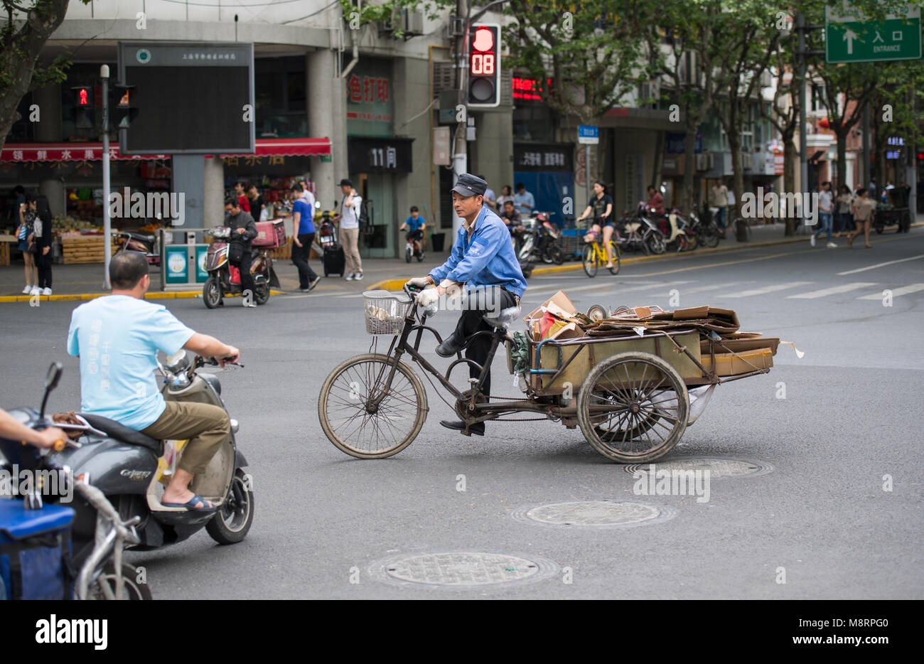 People riding bikes and scooters on the streets of Shanghai in China - Stock Image